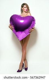 Valentine's Day. Nude beautiful girl with retro hairstyle hiding behind huge volume purple heart. Inflatable balloon in shape of heart.