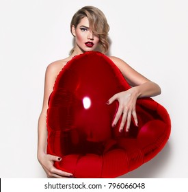 Valentine's Day. Nude beautiful girl with retro hairstyle lurking behind a huge volume of red hearts. Inflatable ball in the shape of the heart.