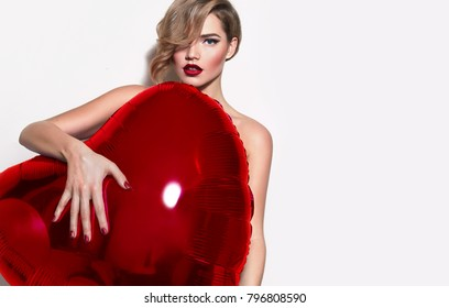 Valentine's Day. Nude beautiful girl with retro hairstyle lurking behind a huge volume of red hearts. Inflatable ball in the shape of the heart.Celebration, congratulation, postcard, fashion, beauty.