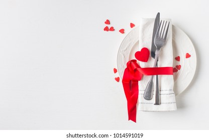 Valentines day (or wedding) meal background with red ribbon, hearts, fork, knife, white plate and napkin. Romantic holiday table setting. Beautiful background with blank. Restaurant concept. Flat lay