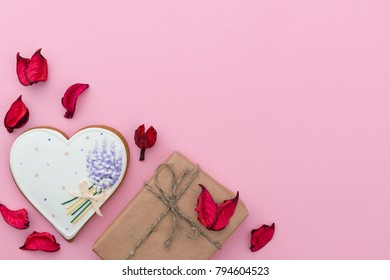 Valentines day pink background with heart shaped sweet cake, gift box and red rose petals