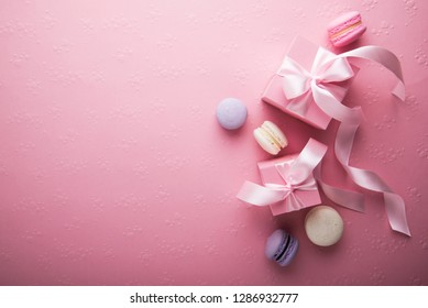 Valentine's Day. Pink gift tied with rosy ribbon and macaron macaroon cookie on pink heart background top view. Valentines Day, 8 March, Womens Day, Birthday, Mothers Day holiday background