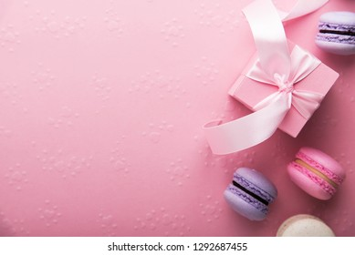 Valentines Day. Pink gift tied with rosy ribbon and macaron macaroon cookie on pink heart background top view. Valentines Day, 8 March, Womens Day, Birthday, Mothers Day holiday background