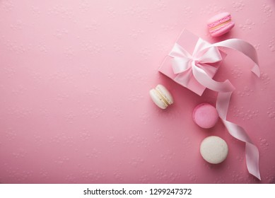 Valentines Day. Pink gift tied with rosy ribbon and macaron macaroon cookie on pink heart background top view. 8 March, Womens Mothers Valentines Day, Birthday holiday background