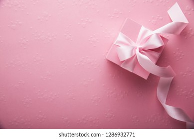 Valentine's Day. Pink gifts presents tied with rosy ribbon on pink heart shape patterned background top view. Valentines Day, 8 March, Women's Day, Birthday, Mother's Day holiday background