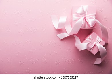 Valentines Day. Pink gifts, presents tied with rosy ribbon on pink heart background top view. 8 March, Valentines Womens Mothers Day, Birthday holiday background