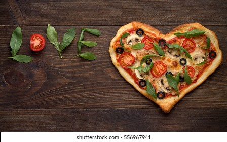 Valentines day pizza in heart shape with inscription love on dark rustic wooden background. Top view, copy space.