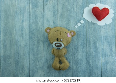 Valentines Day postcard. Teddy Bear and red heart in thought bubble on a wood background.
