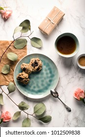 Valentine's Day present and breakfast. Cup of coffee, healthy homemade chocolate chip cookies, pink flowers, parchment paper, handmade blue ceramic tableware from above. Food photography.