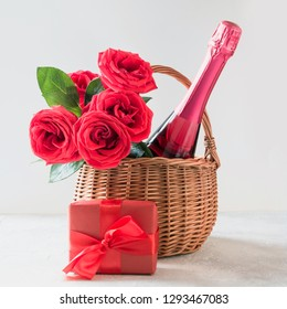 Valentine's day present with gift hamper, bouquet of red roses, champagne, and gift on white.