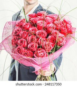 Valentines day or proposal. Young happy handsome man holding big bunch of red roses in his hand on grey background, studio shot