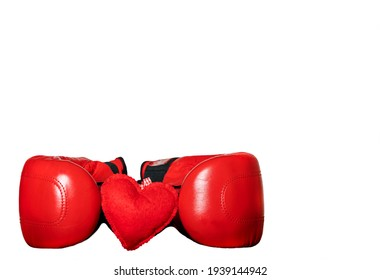 Valentine's Day and red boxing gloves carefully hold a red fabric heart as a symbol of the holiday. Studio photo on a white background banner.