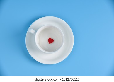 Valentines day. A Red heart in a white cup of coffee on blue background. Copy space. Top view.