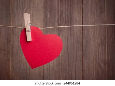 Valentine's Day, red paper heart hanging on the clothesline, wooden background