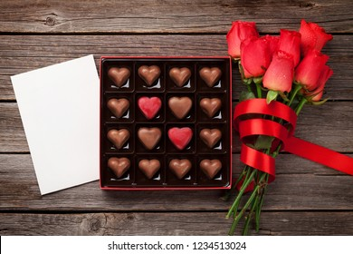 Valentines day with red roses and heart chocolate box on wooden table. Top view with space for your greetings