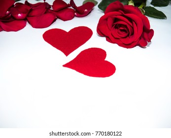 Valentine's day - red roses and two red hearts on a white background
