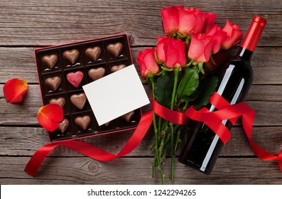 Valentines day with red roses, wine bottle and chocolate box on wooden table. Top view with space for your text