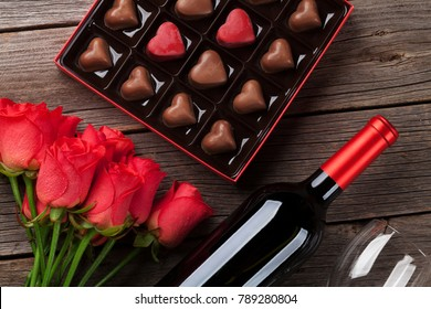 Valentines day with red roses, wine bottle and chocolate box on wooden table. Top view