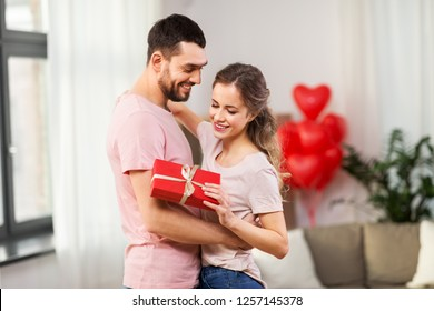 valentines day, relationships and people concept - happy couple with gift box hugging at home