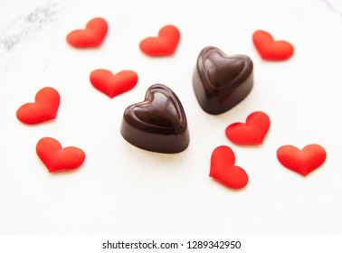 Valentines day romantic background -  chocolate candy and silk red hearts