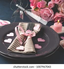 Valentine's day romantic date dinner concept with pink candles and hearts on dark background