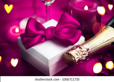 Valentine's Day Romantic Dinner. Date. Table setting with Champagne in two glasses, candles and gift box over holiday purple background with hearts. Wedding celebrating