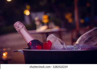 Valentine's Day, Romantic Dinner or Date with Champagne and two glasses, candles and rose petals. Wedding celebrating.