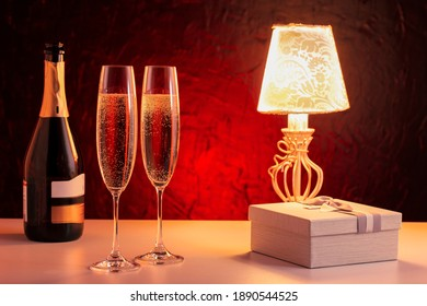 Valentines Day. Romantic luxury evening with champagne and gift on table with magic light.