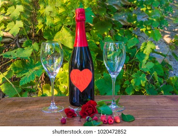 Valentine's day or romantic rendezvous concept/bottle of champagne decorated with red heart, two wineglasses on wooden table outdoors in front of the vine and old well by sunny day