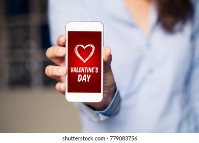 Valentine's day shopping app in a mobile phone screen while woman hold it in the hand.