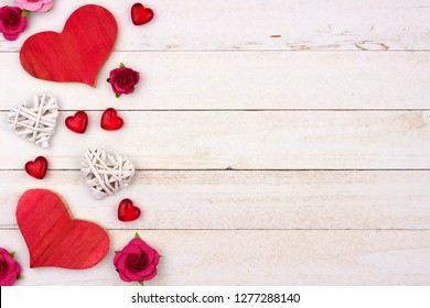 Valentines Day side border of hearts, flowers and decor against a rustic white wood background. Copy space.