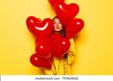 Valentine's day. Smiling girl in yellow sweater giving a kiss, looking out of bunch of red balloons. Isolated over yellow background.
