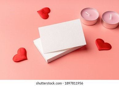 Valentines Day. Stack of visit cards on pink background with hearts and candles for mock up design