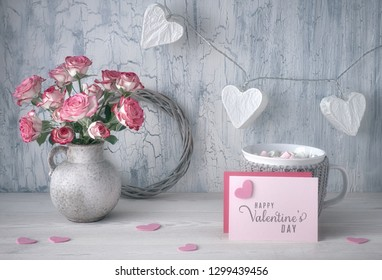 Valentines day still life with blank paper card, pink roses, cup of hot chocolate and garland lights in shape of paper hearts on rustic background