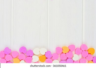 Valentines Day sugar candy hearts forming a bottom border over a white wood background