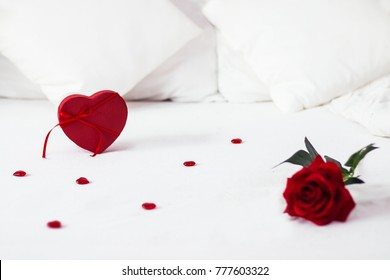 Valentines day surprise at morning on the white bed for her. Red heart gift box background with rose on the front . copy space