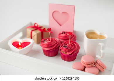 valentines day and sweets concept - close up of cupcakes with red buttercream frosting and heart shaped cocktail sticks, macarons, candle, coffee cup and gift box on tray