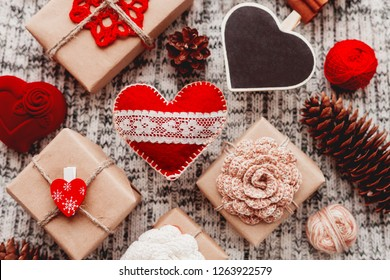 Valentine's Day symbols - hearts, presents in craft paper with crochet flowers, pine cones, red jewelry gift box - on knitted background.