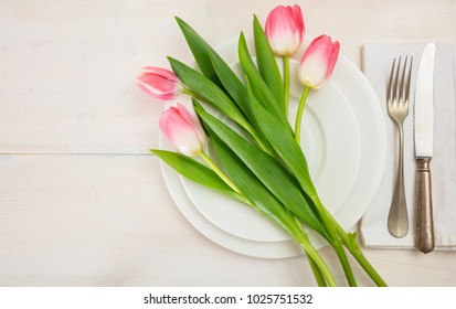 Valentines day table setting with pink tulips on white wooden background. Top view, space for text