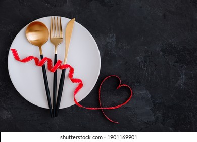 Valentine's Day table setting with plate, gold knife, fork, spoon, red ribbon with heart on dark background, top view, copy space. Valentines day background, holiday concept.