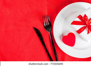 Valentine's day table setting with plate, fork, knife, gift box and red heart, on red tablecloth background top view copy space