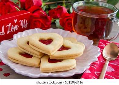 Valentine's Day tea and heart shaped cookies filled with strawberry jam with red roses