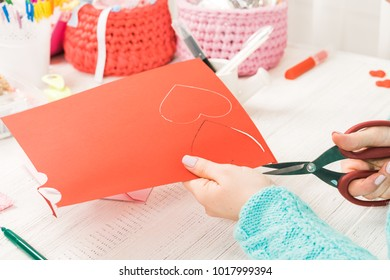 Valentine's day theme. Female hands cut the heart out of the paper. Packed gifts, tools on a battered wooden table. Workplace for the preparation of handmade ornaments