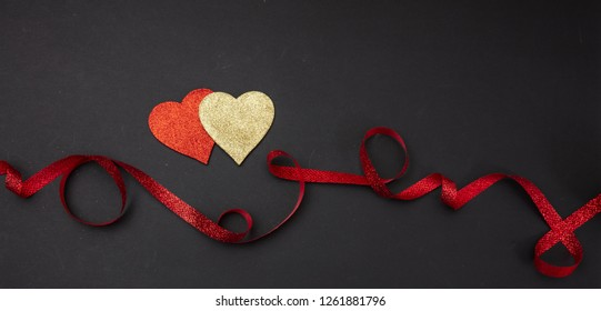 Valentines day.  Top view of red and golden hearts with satin ribbon against black background, isolated, banner, wallpaper.
