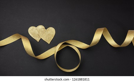 Valentines day.  Top view of two golden hearts with satin ribbon against black background, wallpaper.