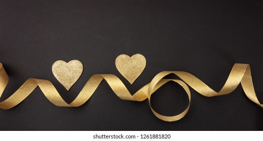 Valentines day.  Top view of two golden hearts with satin ribbon against black background, banner