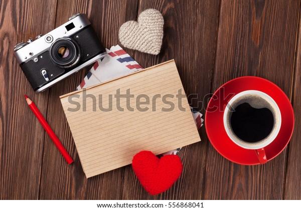 バレンタインデーのおもちゃのハート、カメラ、コーヒー、メモ帳をテキストに使用できます。木のテーブルの上面図