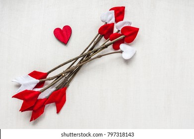 Valentines day twig arrows on white wooden background and red heart. Handmade cupid's arrows.