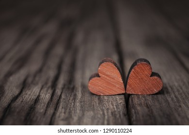 Valentines day two red hearts on old wooden background. Holidays card with copy space.