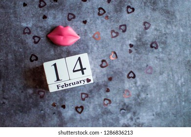 Valentines day vintage white perpetual calendar for february 14 with note for beloved and chocolate pink lips on gray background with copy space for your text